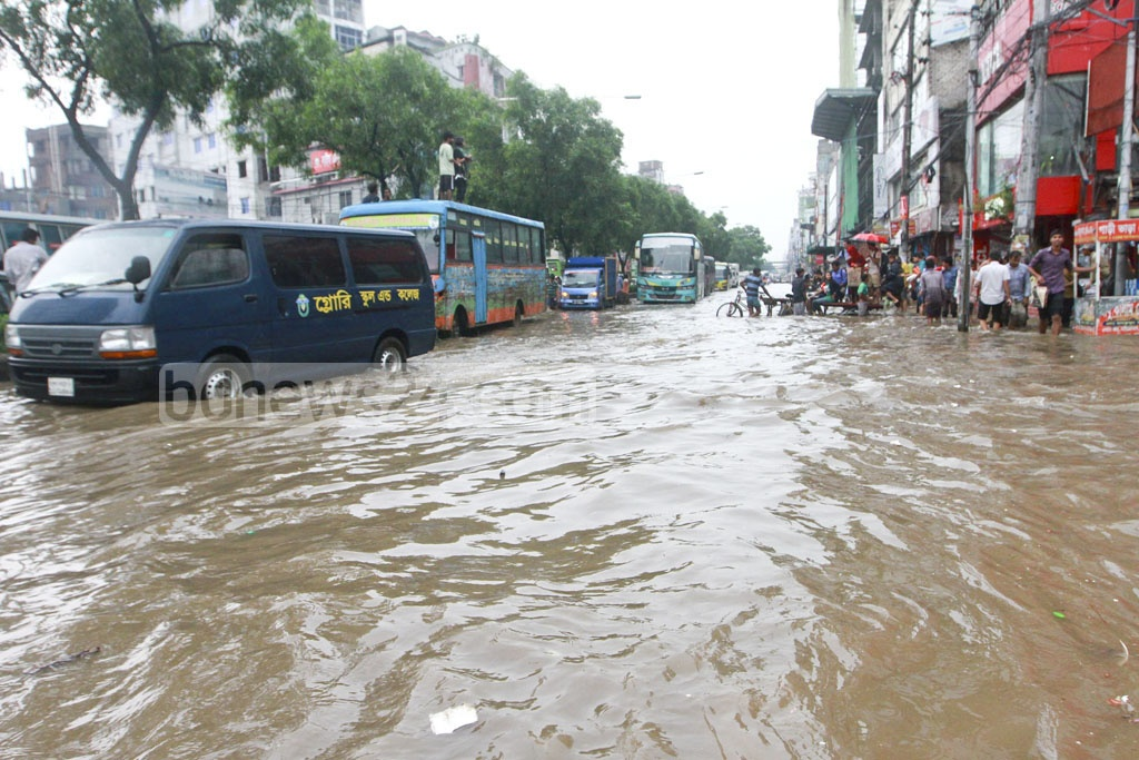 Vehicles and commuters wade through dirty rainwater clogged on a street at Rokeya Sarani in Dhaka's Mirpur. A sudden downpour on Monday morning brought similar scenario in many parts of the city.