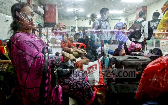 A woman wears an anxious face as she sits surrounded by luggage inside a bus counter at Dhaka's Kalyanpur on Wednesday. Photo: tanvir ahammed