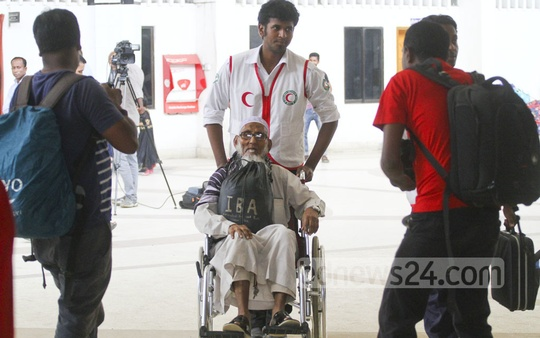 A Red Crescent volunteer helps an elderly passenger on a wheelchair at Dhaka's Kamalapur Railway Station on Wednesday. Photo: abdul mannan