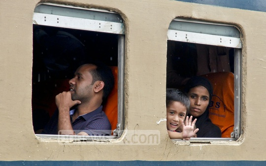 A child waves out of the window of a train carriage leaving Dhaka's Airport Railway Station ahead of Eid on Thursday. Photo: tanvir ahammed