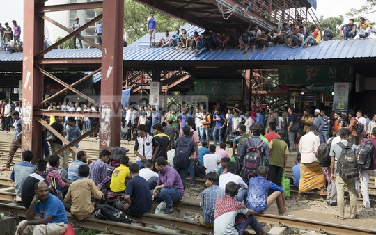 Holidaymakers bound for home to celebrate the Eid with their loved ones wait for trains on the tracks at Airport Railway Station in Dhaka on Friday. Photo: mostafigur rahman