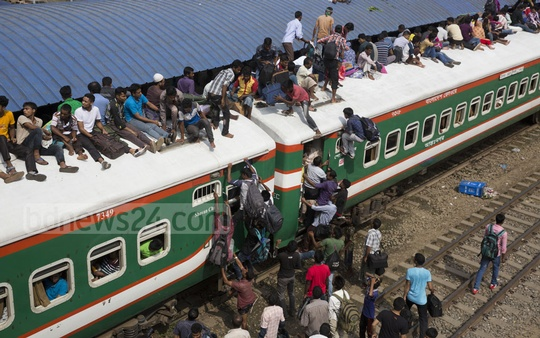 Homebound people risk their lives by climbing on the roof of a train as it leaves Dhaka's Airport Railway Station on Friday. Photo: mostafigur rahman