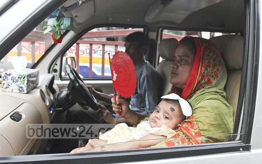 A mother uses a handheld fan to cool off her child as the family spent one and a half hours in the gridlock in a Dhaka street on Thursday.