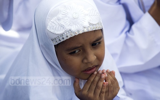 A young girl raises her hands for Eid prayers at the National Eidgah on Monday. Photo: mostafigur rahman
