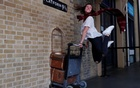 A woman poses for a photograph with the Harry Potter trolley at Kings Cross Station, in London, Britain Jun 26, 2017. The first Harry Potter book, 'Harry Potter and the Philosopher's Stone' was first published 20 years ago. Reuters