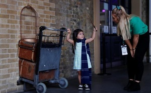 A girl waves a wand at the Harry Potter trolley at Kings Cross Station, in London, Britain Jun 26, 2017. The first Harry Potter book, 'Harry Potter and the Philosopher's Stone' was first published 20 years ago. Reuters