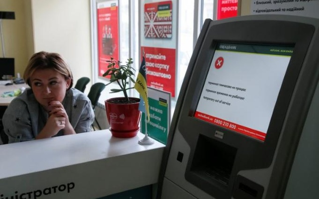 An employee sits next to a payment terminal out of order at a branch of Ukraine's state-owned bank Oschadbank after Ukrainian institutions were hit by a wave of cyber attacks earlier in the day, in Kiev, Ukraine, June 27, 2017. Reuters