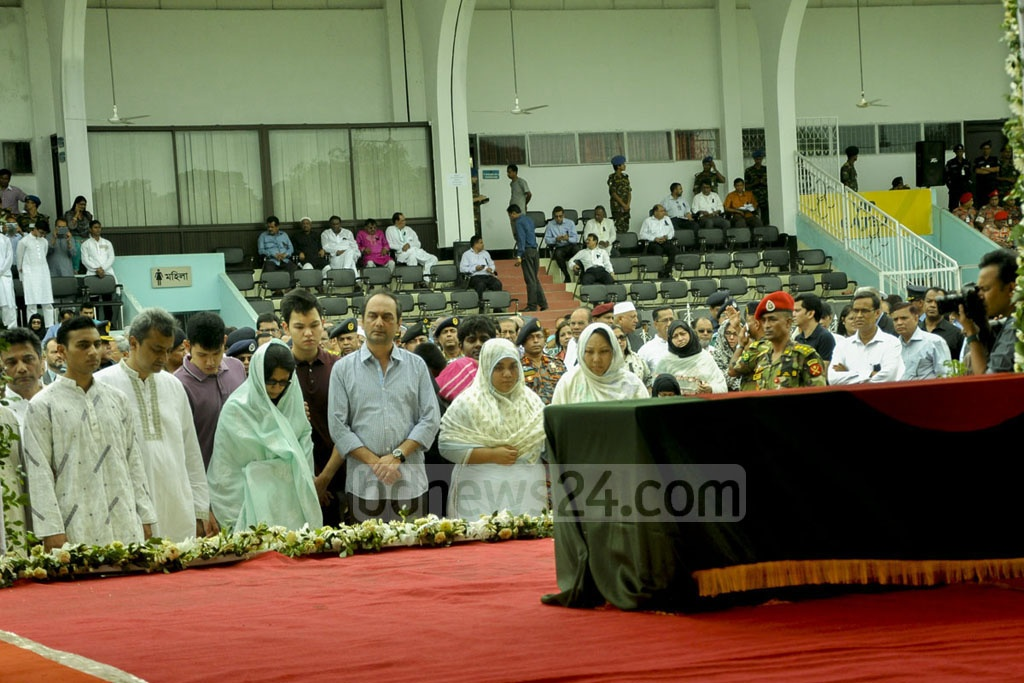 Family members of the attack's three Bangladeshi victims stand before their coffins.