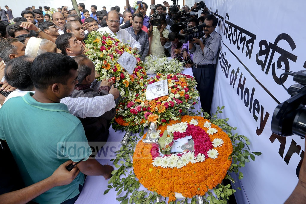 People stood in silence to pay homage at the site that used to house Holey Artisan Bakery and O' Kitchen restaurant in Gulshan where 22 people were killed in a Islamist terrorist attack. The site was opened for four hours for the visitors on Saturday. Photo: asaduzzaman pramanik