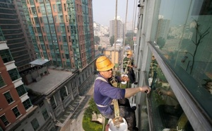 FILE PHOTO: Workers clean the windows of an apartment block in Beijing, China, June 27, 2017. Reuters