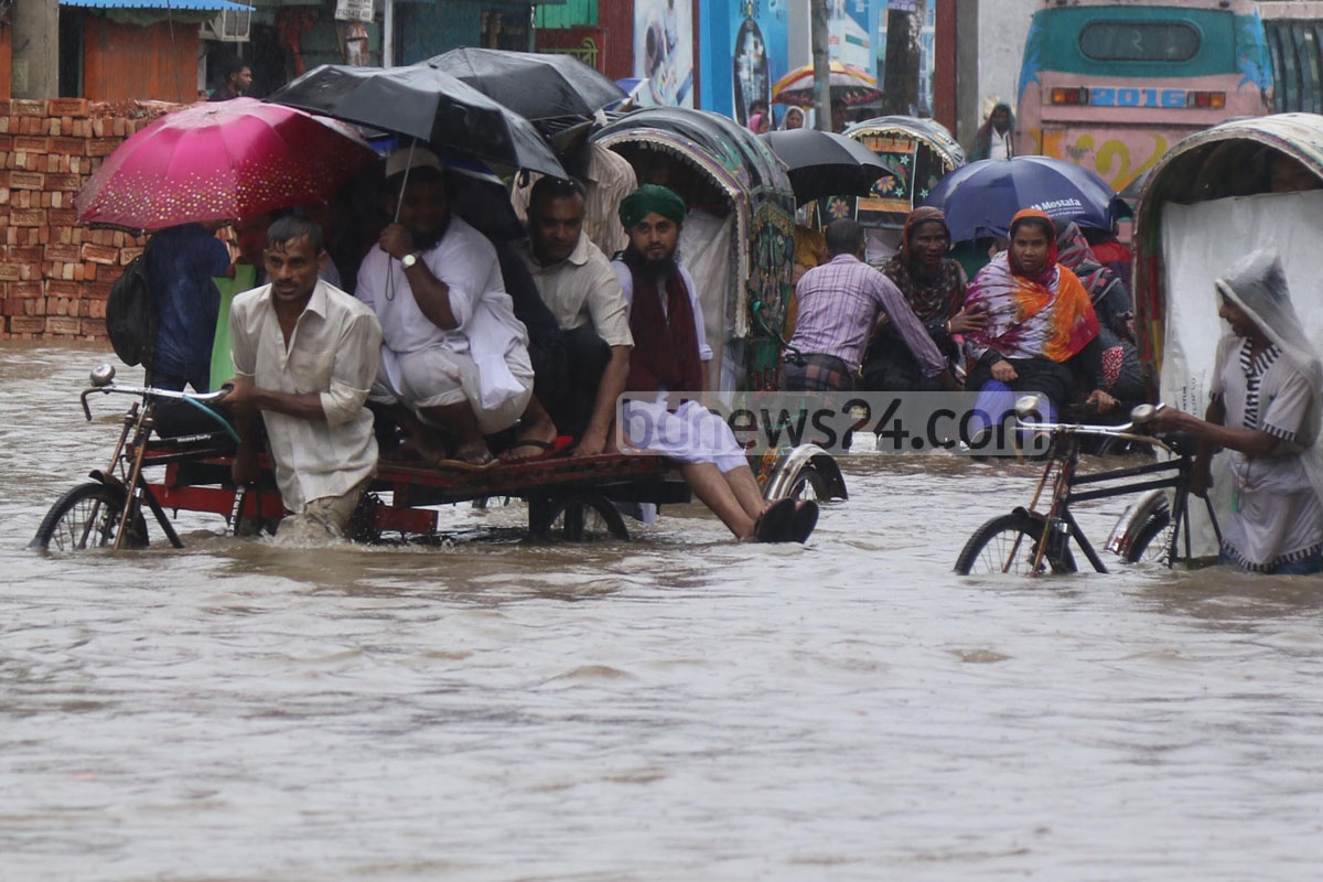 Rickshaws and pedestrians take the trouble to wade through the flooded roads. The photo was taken at Gate 2 of the port city on Monday. Photo: suman babu