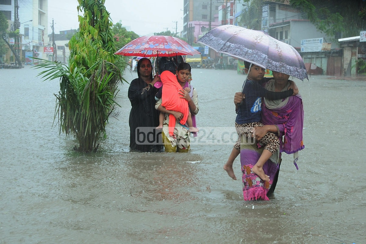 With children on lap, women wade through knee-deep water amid rain at Agrabad Access Road on Monday. Photo: suman babu