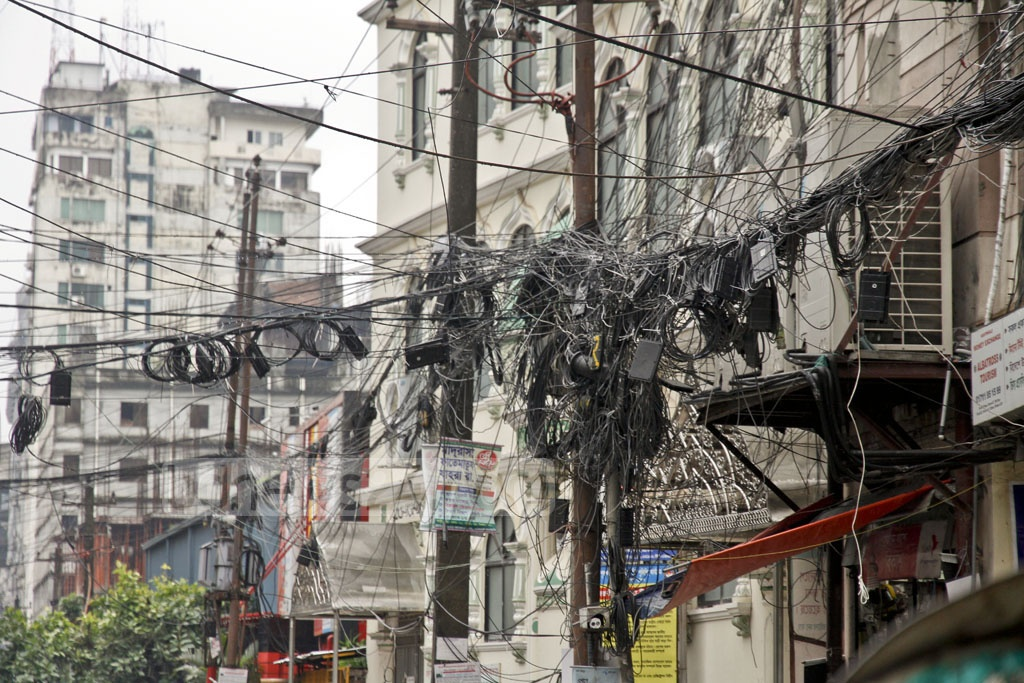 An electric pole is being used at Uttara on Tuesday to hang internet, cable TV and telephone wires dangerously, raising possibilities of accidents.