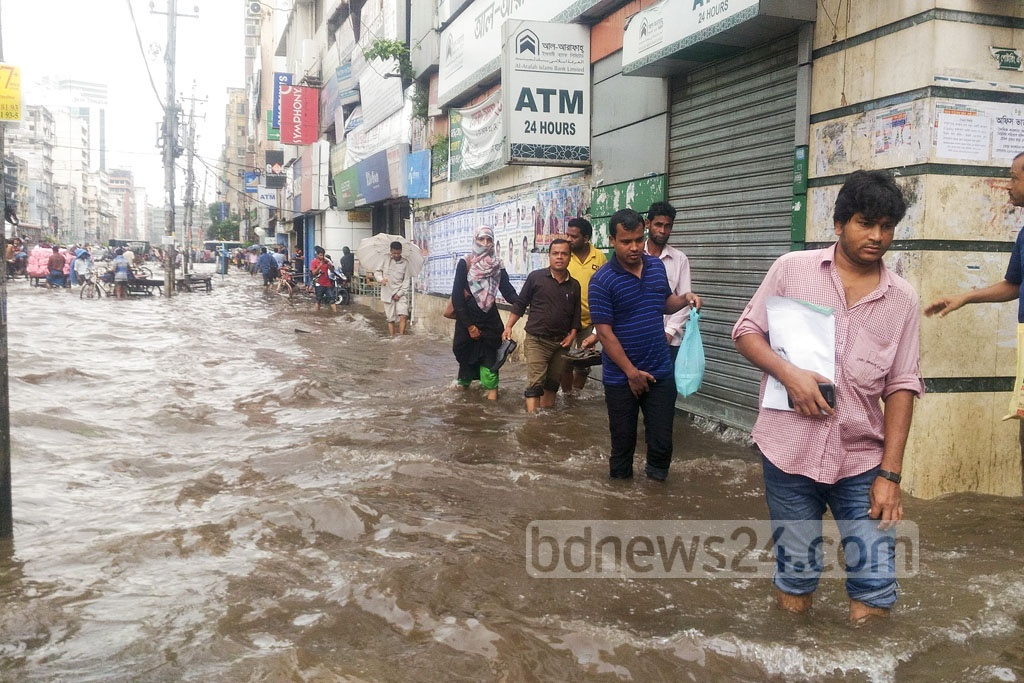 People in the capital started a hazardous morning commuting on Wednesday as many roads went under knee-deep water following an overnight downpour. The photo is taken from Motijheel. Photo: asif mahmud ove