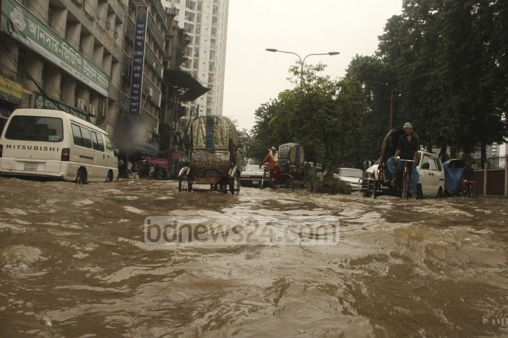 People in the capital started a hazardous morning commuting on Wednesday as many roads went under knee-deep water following an overnight downpour. The photo is taken from Razarbagh Police Line area.