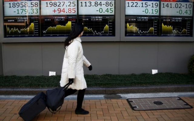 A woman walks past electronic board showing stock prices and Japanese Yen's exchange rate outside a brokerage at a business district in Tokyo, Japan, Jan 23, 2017. Reuters