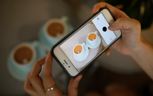 A woman takes photographs of creamarts made by South Korean barista Lee Kang-bin at his coffee shop in Seoul, South Korea, June 30, 2017. Reuters