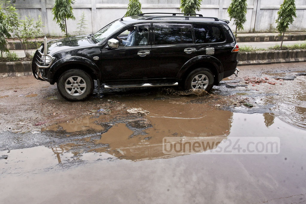 Many parts of the old airport-Rokeya Sarani link road are full of potholes but some of the 'ditches' are so deep that it might cause serious accident at any time specially when driving at night. The photo is taken on Friday.