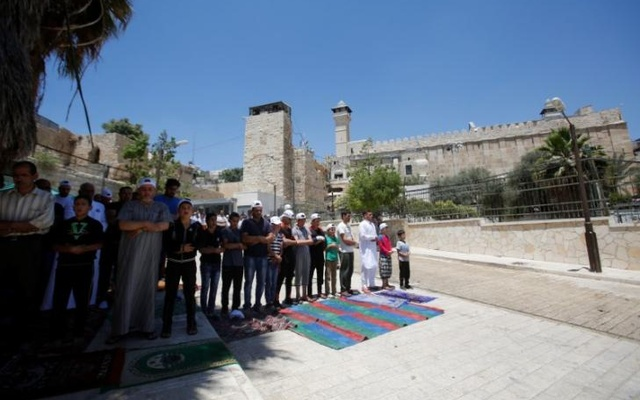 FILE PHOTO: Palestinians attend the Friday prayer outside al-Ibrahimi mosque, which Jews call the Tomb of the Patriarchs, in the West Bank city of Hebron June 16, 2017. REUTERS/Mussa Qawasma/File Photo