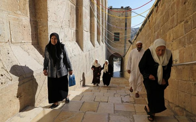 Palestinians walk outside al-Ibrahimi mosque, which Jews call the Tomb of the Patriarchs, in the West Bank city of Hebron July 7, 2017. REUTERS/Ammar Awad