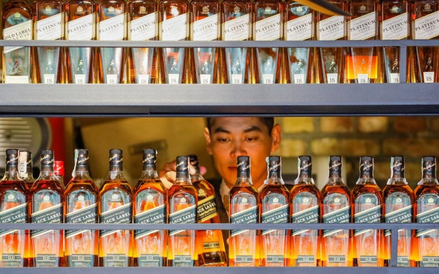 A bartender takes a bottle of Johnnie Walker whisky at Barmaglot bar in Almaty, Kazakhstan June 22, 2017. REUTERS