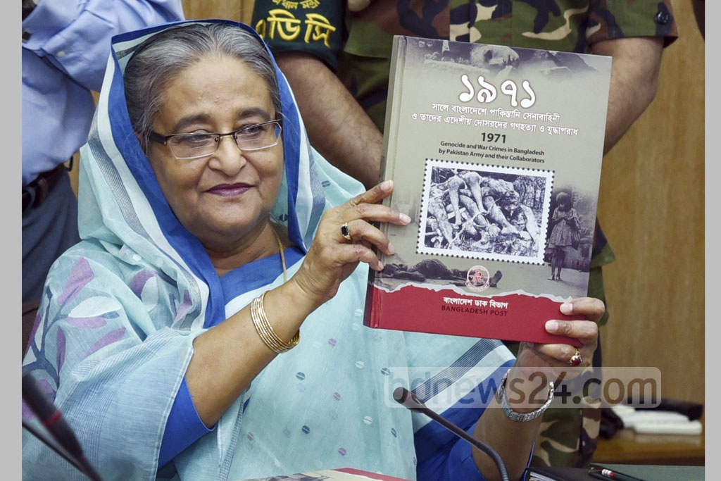 Prime Minister Sheikh Hasina unveiled an album of special commemorative postal stamps titled 'Gonohotya O Juddhaporadh' (Mass Murder and War Crimes) on Monday. Photo: Saiful Islam Kallol