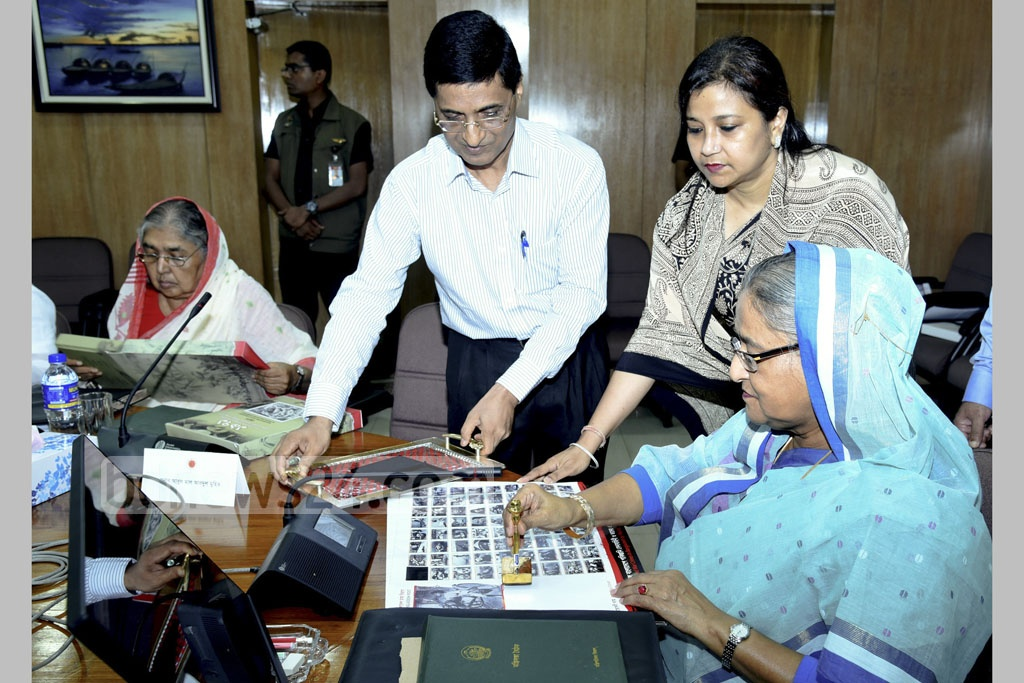 Prime Minister Sheikh Hasina unveiled the inaugural envelope containing 71 commemorative postal stamps with photos of mass murders committed during independence war at the cabinet meeting on Monday. Photo: Saiful Islam Kallol