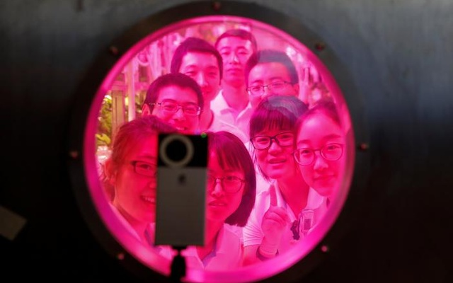 Volunteers smile to a camera from inside a simulated space cabin in which they temporarily live as a part of a scientistic Lunar Palace 365 Project, at Beihang University in Beijing, China July 9, 2017. REUTERS/Damir Sagolj