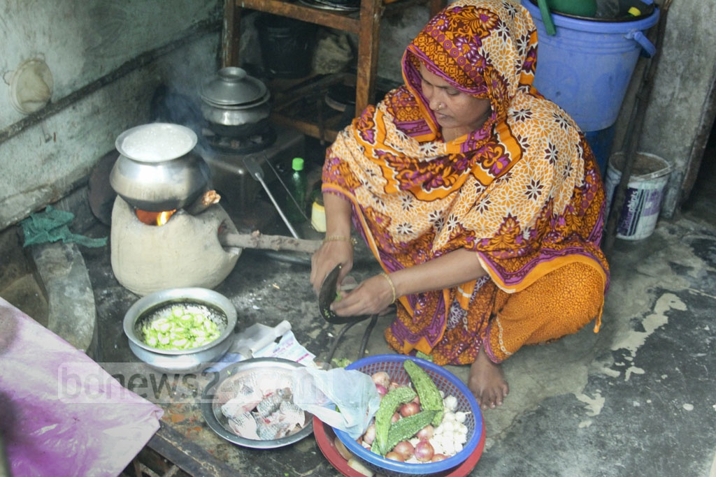 A woman cooks on a clay stove beside a gas cooker at her home in Dhaka's Kaziparha on Thursday. Gas supply to Mirpur was stopped for over 15 hours due to metro rail construction. photo: asif mahmud ove