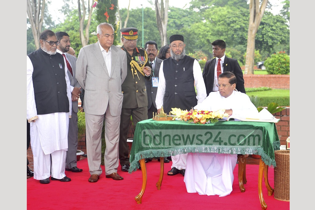 Sri Lankan President Maithripala Sirisena signs the visitor's book at National Memorial in Savar after paying respects on Thursday. Photo: PID
