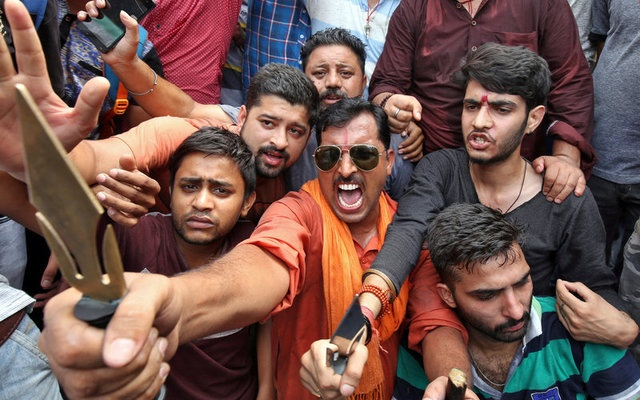 People react as they hold tridents and shout slogans during a protest organised by Hindu nationalist group Vishva Hindu Parishad (VHP), against Pakistan after seven Hindu pilgrims were killed in a gunbattle that erupted in Kashmir on Monday, in Jammu July 11, 2017. Reuters