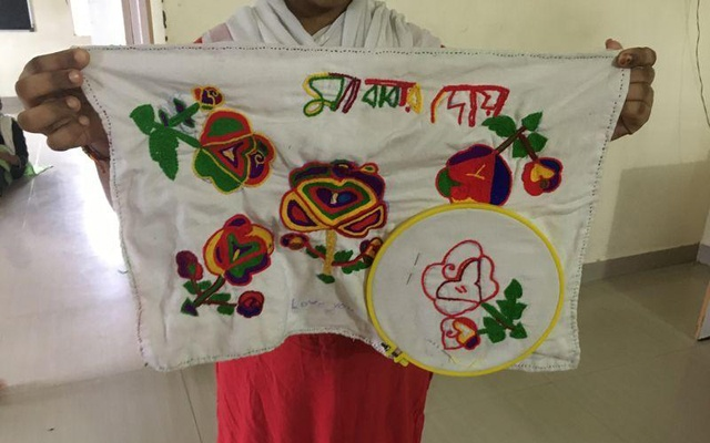 "Girls from Bangladesh who were sex trafficked to India at a shelter home for rescued girls in Pune in Maharashtra, India, show a cloth on which they have embroidered Bengali words - ""Mother and father's kindness"" - THOMSON REUTERS FOUNDATION/ROLI SRIVASTAVA"