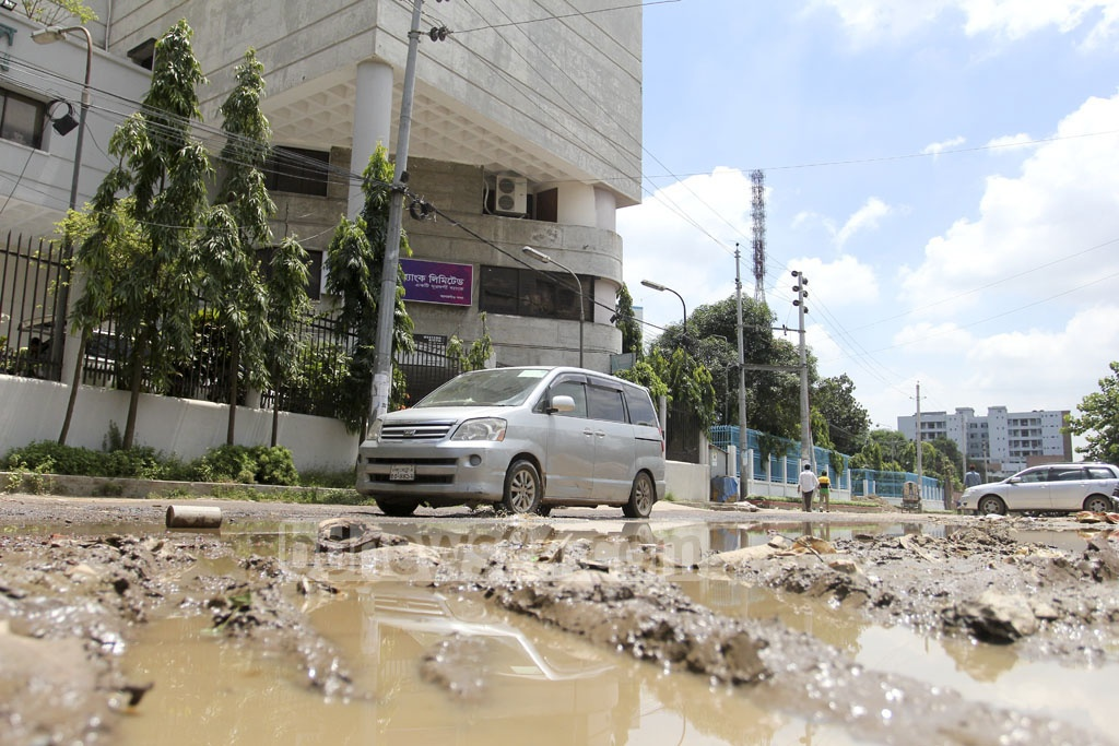 Vehicles struggle to ply the run-down street in front of the PKSF headquarters in the capital's Agargaon on Sunday. Photo: asif mahmud ove