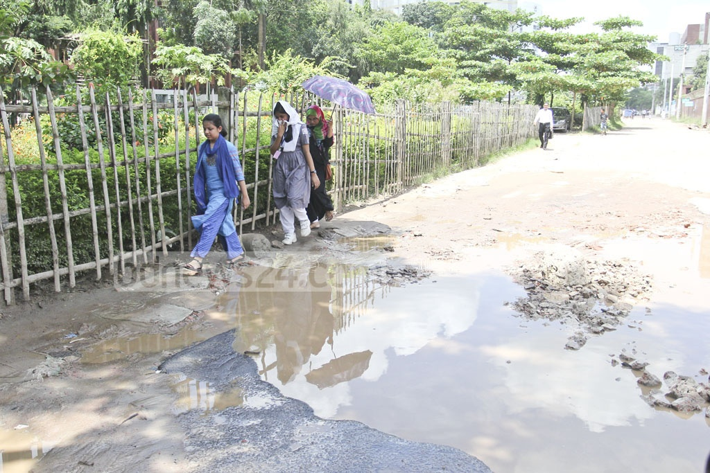 Pedestrians struggle to walk on the waterlogged street in front of the Department of Environment on Sunday. Photo: asif mahmud ove