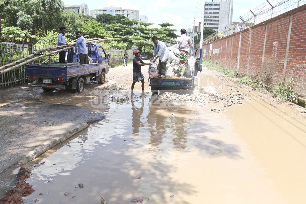 Workers put brick chips to fill potholes in an attempt to repair temporarily the waterlogged street in front of the Department of Environment on Sunday. Photo: asif mahmud ove