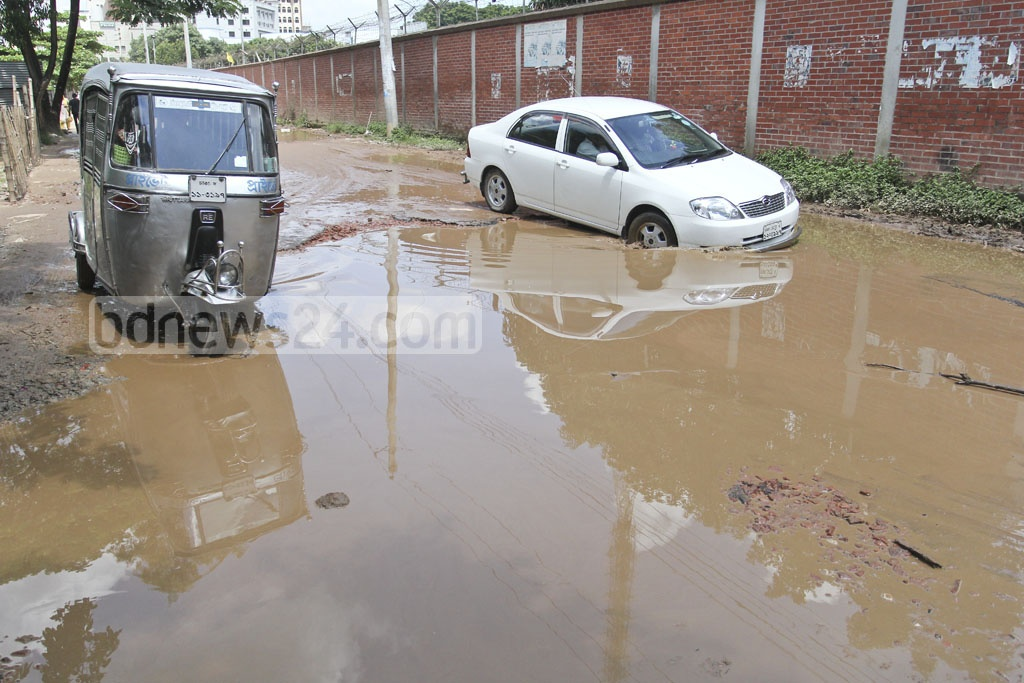Vehicles navigate potholes on the waterlogged street in front of the Department of Environment on Sunday. Photo: asif mahmud ove