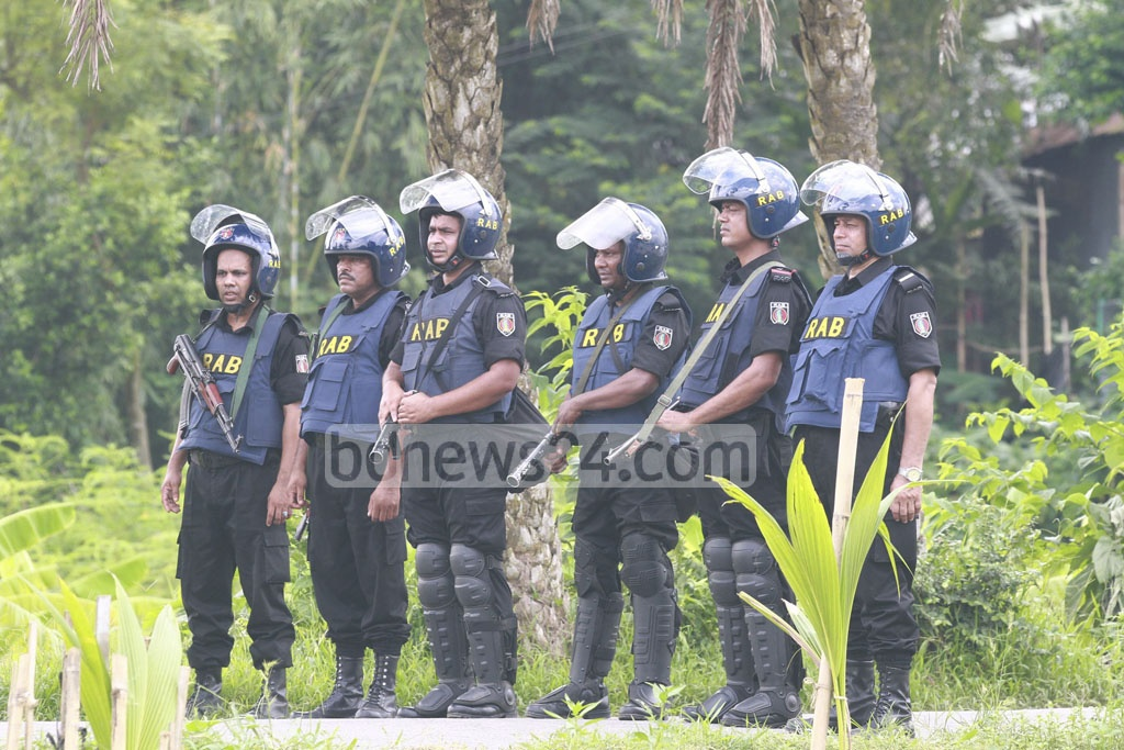 RAB personnel stand guard around a suspected militant den at Ashulia in Savar on Sunday.