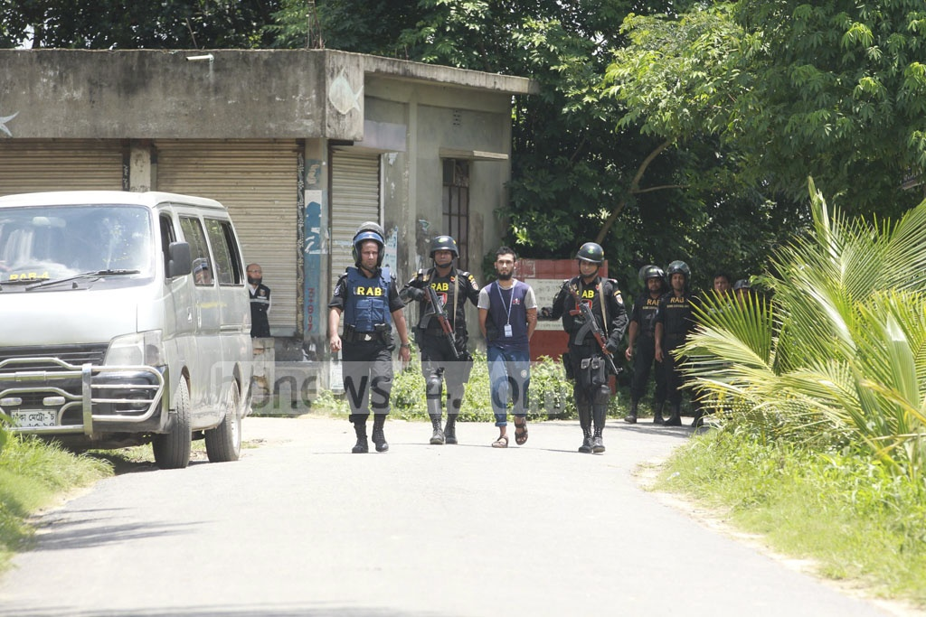 RAB personnel taking to vehicle one of the four suspected militants, who surrendered after an 11-hour siege to their hideout at Ashulia in Savar on Sunday.