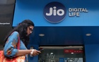 A woman checks her mobile phone as she walks past a mobile store of Reliance Industries' Jio telecoms unit, in Mumbai, India, Jul 11, 2017. Reuters