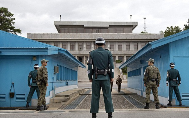 South Korean soldiers (front) keep watch at a North Korean soldier at the truce village of Panmunjom, in the demilitarized zone separating the two Koreas in Paju, north of Seoul April 4, 2013 in this picture provided by Yonhap. Reuters