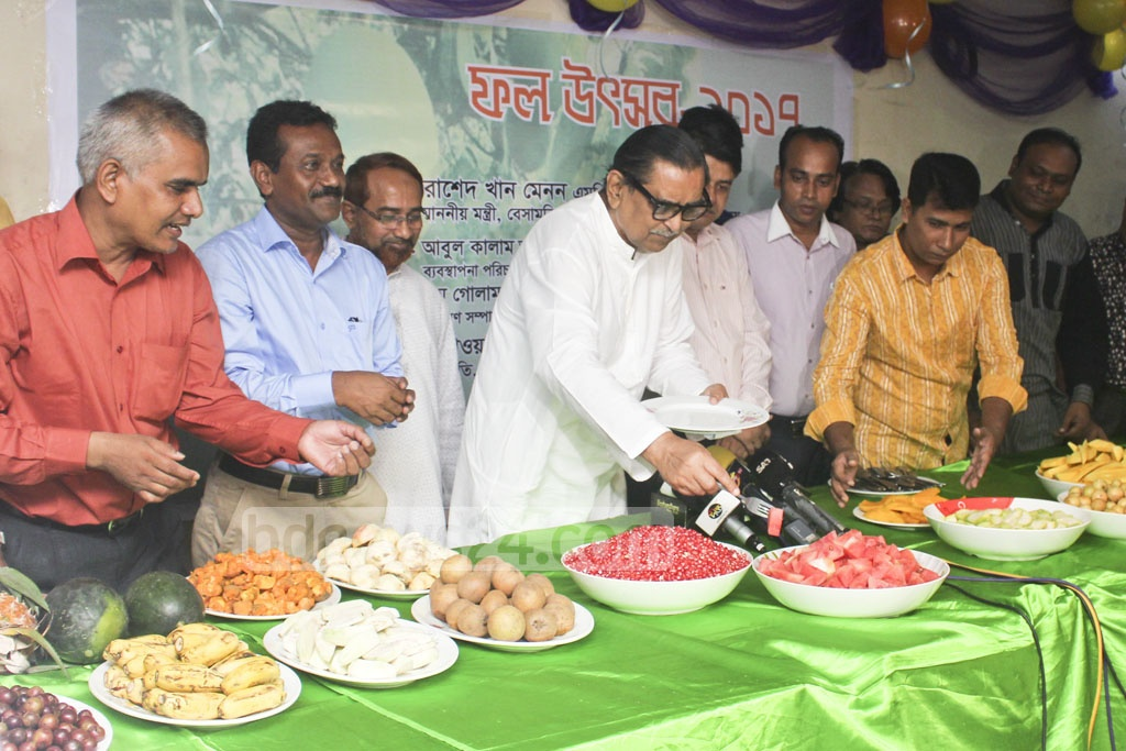 Tourism Minister Rashed Khan Menon, who was invited as chief guest of a fruit festival in Dhaka Reporters Unity, tastes locally-grown fruits with reporters on Wednesday.