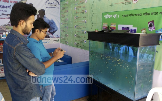 A man takes photo of fishes kept in an aquarium while another visitor looks on in a stall at the fair. Photo: abdul mannan