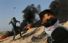 A Palestinian protester uses a sling to hurl stones towards Israeli troops during clashes near the border between Israel and central Gaza Strip Jul 21, 2017. Reuters