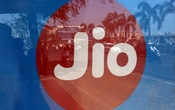 Commuters are reflected on an advertisement of Reliance Industries' Jio telecoms unit, at a bus stop in Mumbai, India, Feb 21, 2017. Reuters