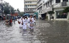 Students wade through knee-deep stagnant rainwater on a road in Chittagong's Agrabad neighbourhood on Saturday. Photo: suman babu