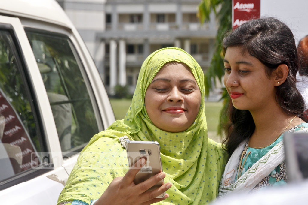 Students of RAJUK Uttara Model College try to find out their HSC results via text message on the phone. Photo: tanvir ahammed