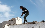 A fighter of Libyan forces stands atop the ruins of a house as the forces secure the last few buildings where Islamic State militants had been making a final stand, in Ghiza Bahriya district in Sirte, Libya Dec 6, 2016. Reuters