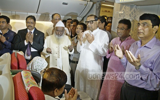 Religious Affairs Minister Motiur Rahman, Civil Aviation and Tourism Minister Rashed Khan Menon pray with pilgrims before they head to Saudi Arabia on this year's first Hajj flight.
