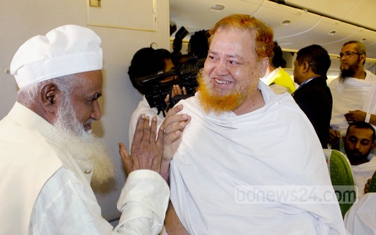 Religious Affairs Minister Motiur Rahman speaks to an elderly pilgrim headed to Saudi Arabia on Biman's first Hajj flight this year.