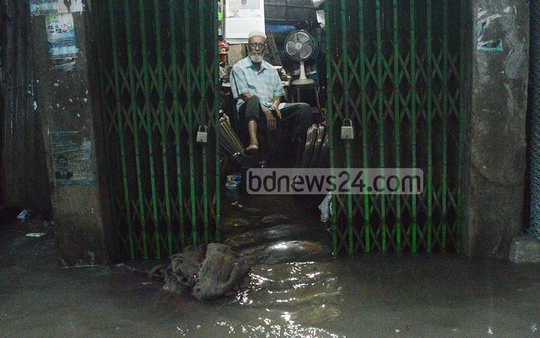 A man sits in a shop at Khatunganj flooded by rainwater while the city experienced heavy downpour on Monday. Photo: suman babu